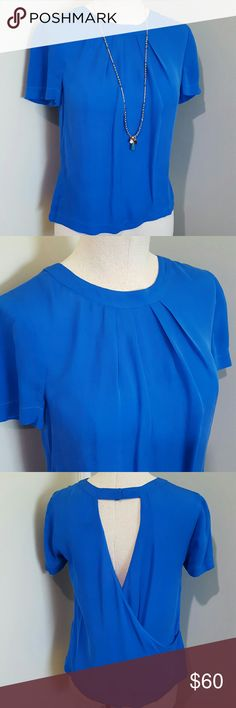 """J.Crew Open Back Blue Silk Blouse 00 Stunning blue silk blouse by J.Crew.  size 00 or XS but can also fit a size because it's so loose.  100% silk.  Bright summer blue color. High round neckline, pleated front, short sleeves, loose flowy body.  The back has a stunning draped wrap around reveal.  Snap neckline closure on back. Excellent condition, no flaws! Measures 36"""" bust, 22"""" length. J. Crew Tops Blouses"""