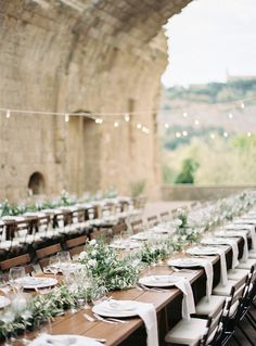 outdoor tablescape under cafe lights with a medieval castle backdrop in Italy | Photography: Katie Grant