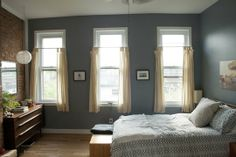 gray walls, white and blue bed. perfect, chill bedroom.