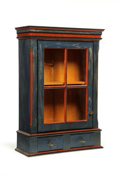 "DECORATED HANGING CUPBOARD.   Tom King, Delaware, Ohio, 20th century, pine. One four-pane door over two drawers, with red and blue paint. 37""h. 25.5""w. 10""d."