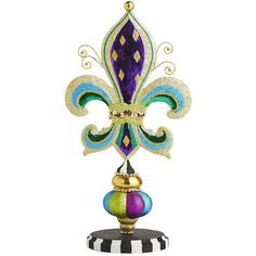 Traditionally a symbol of royalty, the <i>fleur-de-lis</i> has been lovingly embraced by Mardi Gras revelers everywhere. During the reign of King Louis IX, the three petals were said to represent faith, wisdom and chivalry. To that we've added a traditional jester pattern and a touch of sparkle, making our tabletop decoration the whole package.