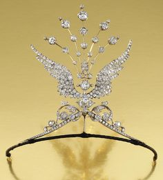 DIAMOND WING AIGRETTE TIARA, 1900s Pair of opposing scrolls surmounted by 2 out wept wings terminating in an aigrette of radiating knife-edge bars set throughout w/ circular-cut diamonds. Orig fitted case, 2 brooch pin fittings, 3 tiara frame attachments, a diamond-set suspension bail and a hair pin/aigrette fitting, tiara/aigrette all detachable and may be worn in 5 combinations, wings detachable for wear as individual brooches.