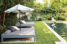 Black and white striped loungers and umbrellas look resort-chic in this stunningly lush green backyard. Tour more of Sara Ruffin Costello's Striking and Stylish New Orleans Home on Our Style Guide here.