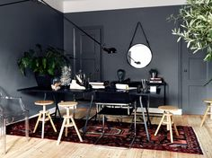 Dark gray work room with light floors and mixed chairs.