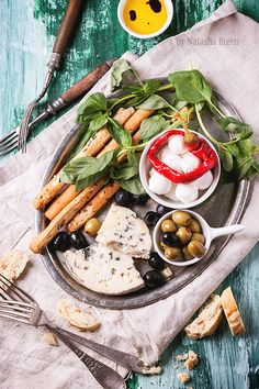 Mixed antipasti blue cheese, olives and mozzarella served on silver tray over green wooden table with vintage forks. Top view.