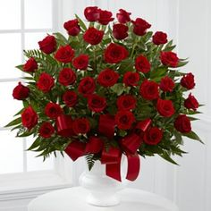 The Soul's Splendor Arrangement is a rich display of the love shared throughout the life of the deceased. Brilliant red roses are elegantly displayed in a white designer plastic urn and accented with lush greens and red satin ribbon Red Rose Arrangements, Rosen Arrangements, Funeral Flower Arrangements, Funeral Flowers, Wedding Arrangements, Wedding Table Centres, All Flowers, Church Flowers, Amazing Flowers