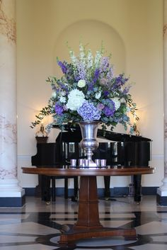 dramatic silver urn flowers wedding centrepiece of tall ivory and purple delphiniums, ivory and purple hydrangeas and stocks, from wedding reception at Botleys Mansion. Botleys Mansion wedding flowers photo.