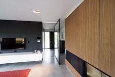 Grote glazen pivoterende deur op maat met een zwarte kader en transparant glas.