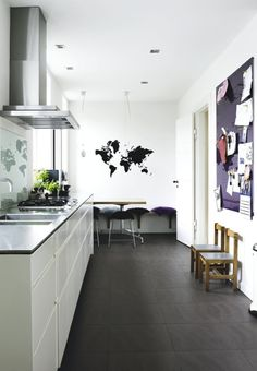 Classic white kitchen but with a contrasting floor in black. The black/white base makes the perfect background for adding colours in the interior as you'd like.
