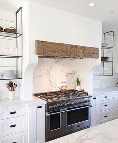 Luxury Small Kitchen Plaster hood with rough hewn beam insert. The Range Hood GuideBECKI OWENS - From dramatic statement hoods or those with a simple minimalist design, today I am sharing inspirations for range hood designs you might consider. Kitchen Hoods, New Kitchen, Kitchen Decor, Kitchen Shelves, Kitchen Ranges, Kitchen Ideas, Kitchen Cabinets, Kitchen Designs, Kitchen Mantle
