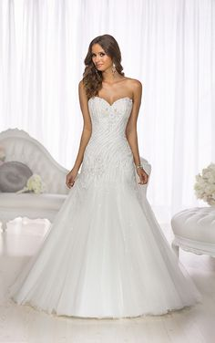 This Essense of Australia designer A-Line wedding dress features a sweetheart neckline and modern, wind-swept beading along its fitted bodice and drop waist. The light-as-air Tulle skirt creates drama, beauty, and movement. The back zips up under elegant crystal buttons, and you can customize this wedding gown to best reflect your sophistication and unique style with color choices in ivory or white.