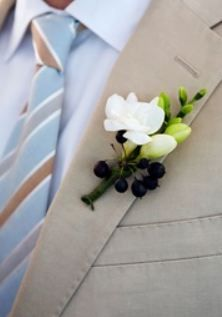 A boutonniere of freesia and hedera berries adds the perfect touch of outdoor elegance to the grooms tan suit.