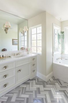 Elegant bathroom features a cream washstand adorned with round mirrored hardware topped with white marble under a full length polished nickel mirror illuminated by Alexa Hampton Ginger Single Arm Sconces alongside floors clad in white and gray chevron tiles.