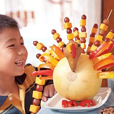 THANKSGIVING TURKEY FRUITY TABLE CENTREPIECE: Great idea to use fruit kebabs to make a turkey centrepiece so kids can grab a fruity treat.