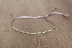 This is a Handmade silk cord bracelet made of tiny 99% pure silver beads and 1 oval sterling silver bead Ending.  This bracelet is adjustable.  Its