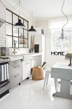 industrial modern kitchen from flor.com love the mix of metal cupboards, industrial lighting and white walls.