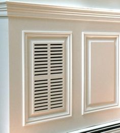 An attractive air return vent in custom made raised panel wainscoting.