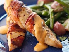 bacon wrapped chicken with chile cheese sauce.... the veggies in the background make it seem not as bad for you as it probably is haha