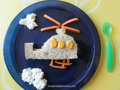 Helicopter---- A helicopter body is made of a peanut butter sandwich, then baby carrots were positioned for the blades atop the helicopter as well as the feet.  Windows are sliced string cheese and clouds are made of cottage cheese.
