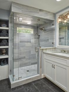 HGTV features this master bathroom with glass and Lena white marble shower, gray limestone floors and quartzite and white wood vanity.
