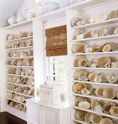 A collection of more than 100 antique jelly molds, in shades of ivory, cream, and white displayed on white, built-in bookshelves. (Photo by Tria Giovan for Cottage Living via myhomeideas.com)