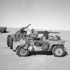 An SAS jeep in the Gabes-Tozeur area of Tunisia. The vehicle is heavily loaded with jerricans of fuel and water, and personal kit. The 'gunner' is manning the .50 inch Browning heavy machine gun, while the driver has a single Vickers 'K' gun in front, and a twin mounting behind.