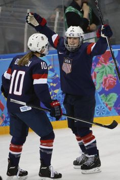 Monique Lamoureux of the Untied States celebrates her goal against Switzerland with teammate Meghan Duggan of the Untied States during the first period of the 2014 Winter Olympics women's ice hockey game at Shayba Arena, Monday, Feb. 10, 2014, in Sochi, Russia. (AP Photo/Petr David Josek)