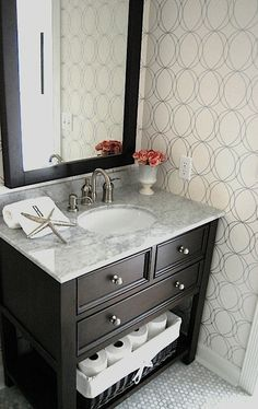 """Graham Brown Darcy White Silver Wallpaper, white carrara marble counter top, white carrara marble hexagon polished 1"""" tiles, espresso Costco bathroom vanity, Price Pfister Amherst brushed nickel faucet, Overstock espresso Hudson mirror, West Elm monogrammed towel, vintage alabaster vase and silver starfish. Espresso, brown, silver, white, gray bathroom colors."""