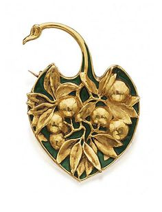 RENÉ LALIQUE | Gold and enamel brooch - circa 1900. Designed as a palm leaf molded with a spray of leaves and berries against a green enamel ground.