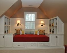 Making the most of limited space in an attic by incorporating the bed and storage into one large built in piece of furniture.