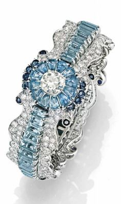 AQUAMARINE SAPPHIRE AND DIAMOND BRACELET, Semi-flexible, to decorations with flowers and scrolls set with sapphires and round diamonds, aquamarines baguette and set in the center with a diamond. Mount platinum and white gold.