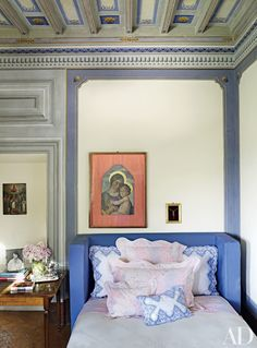 Beneath the painted-wood ceiling of a guest room in decorator Dede Pratesi's Tuscan villa is a custom-made bed dressed with embroidered shams and scalloped bedding by her family's firm, Pratesi.