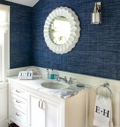 hamptons mansion - love the textured dark blue wallpaper in the powder room with white vanity and marble top