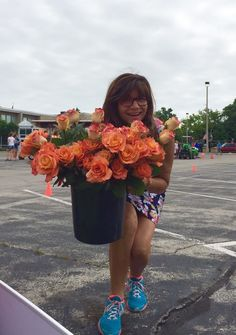 """Deb Fowler, """"The Flower Lady,"""" with a bucket of long-stem roses."""