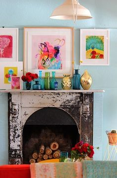 A sweet boho space with lots of colorful art!  I just love the glass bottles and the vintage mantle.