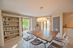 Dining room with old wooden table and modern clear dining chairs in Provençal vacation rental house in a hilltop village in France.