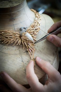 Positioning the jewelry structureof the Flamant Corail necklace.Photo © Van Cleef & Arpels. https://www.yatzer.com/golden-hands-van-cleef-arpels