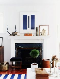 Layered mantel styling | Lidded decorative boxes are a great way to add height to a styled space while hiding small items like keys and remote controls