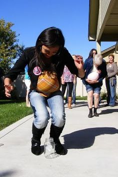 Tinkle in the Pot | Hilarious Baby Shower Game. Each player puts a balloon under their shirt while holding a ping pong ball between their knees. Player must waddle down the line and drop the ball into a jar.
