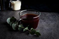 Black tea in glass teacup with eucalyptus flower on table. #food #foodphotography #freestock #blacktea #tea #cupoftea #autumn #fall