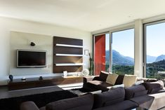 Modern living room design with amazing mountainside view through large windows.