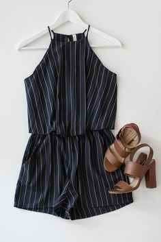 Dark navy blue pinstriped romper with a flowy layered top and high neckline. Keyhole back with button closure. Side pockets. Made with cool and lightweight non-stretch material. Stretchy and elasticated waistband. 100% Polyester Made in USA