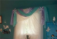 Mermaid Room with gauzy ruffled curtain on small window with turquoise glittery drape and lavender gauzy drape at the top with white real star fish.  Tie backs and fastened with turquoise silky ribbon.