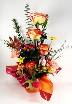 A floral fiesta of orange yellow roses, gathered with seasonal fall flowers.