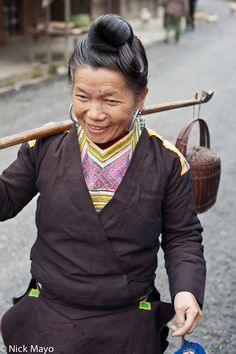 Old Style Dress Of Cenzui Area Kazhai, Guizhou, China (2010)  A Kazhai Miao woman with oversized earrings and a traditional hairstyle carrying a gift by shoulder pole to baby shower.