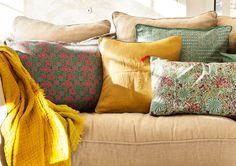 Detalle de cojines mostaza, azul y rosa en sofá beige y con plaid amarilla