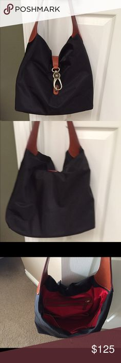 """Dooney & Bourke black fabric and leather bag❤️ DB black fabric and leather bag! Super cute and light weight only used one time and in great condition ! Leather handle strap and a big clasp closure! Red fabric lining with zip pocket and 4 slot pockets for cell phone or sunglasses etc. 4 gold button feet on bottom of bag ! A bag you will sure to enjoy for years! Dimensions are 12""""h x 16""""w x 5""""d and handle drop 8""""❤️ Dooney & Bourke Bags Shoulder Bags"""