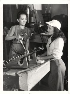 """1943- Girls shown working in the airplane wing production line at the Hudson Motor Car Company in Detroit where Curtiss-Wright """"Helldivers"""" are being built."""