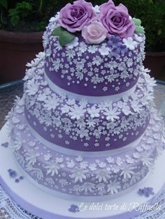 Sweet three tier cake with sugar pasted flowers scattered on the tiers.  Roses on top are a great finish.      ᘡղbᘠ