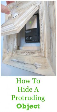 Step by step directions using a old frame and hardware to conceal a protruding object on the wall. (We converted part of our garage into a office/mudroom so we decided to hide the garage door opener since we don't use it)